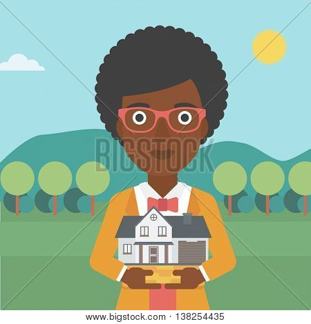 Young woman holding house model in hands on the background of mountains. Real estate agent with house model in hands. Vector flat design illustration. Square layout.