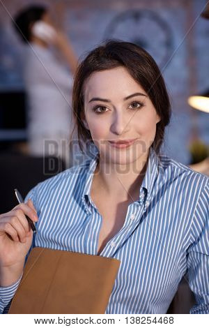 Portrait of attractive young businesswoman, looking at camera.