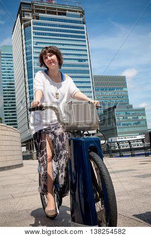 Young woman picks up a hire bike. Canary Wharf London England