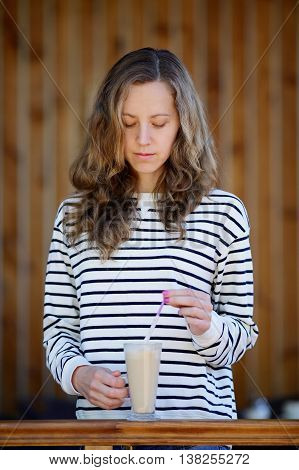 Young Woman With A Cup Of Latte In Her Hands