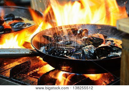 Cooking mussels in a frying pan on a kitchen stove.