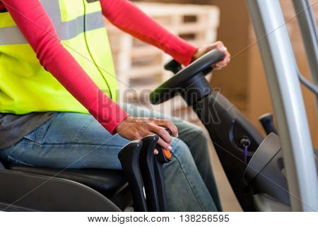 Close up of worker is driving a pallet truck in a warehouse