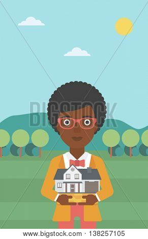 Young woman holding house model in hands on the background of mountains. Real estate agent with house model in hands. Vector flat design illustration. Vertical layout.