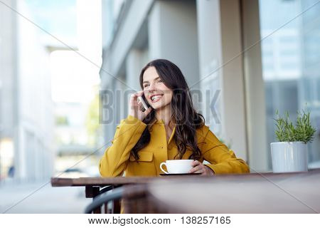 communication, technology, leisure and people concept - happy young woman or teenage girl calling on smartphone and drinking cocoa at city street cafe terrace