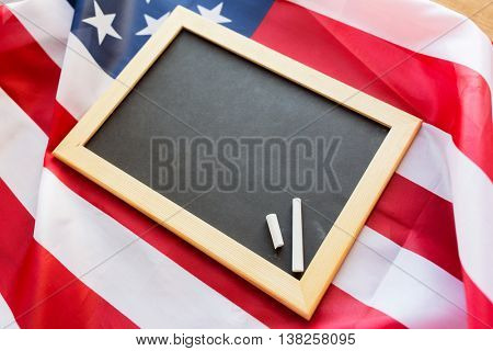 education, election, patriotism, national and memorial concept - close up of blank school blackboard and chalk on american flag