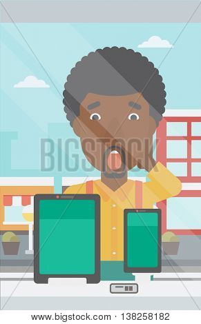 Astonished man looking at digital tablet and smartphone through the shop window. An african-american man with open mouth looking at tablet and phone. Vector flat design illustration. Vertical layout.