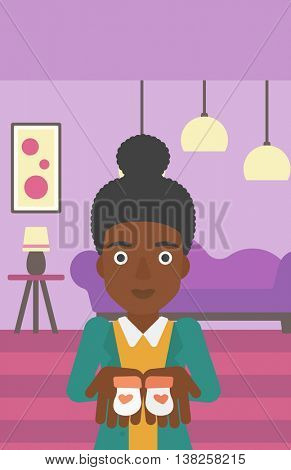 An african-american pregnant woman holding baby booties in hands on the background of living room. Vector flat design illustration. Vertical layout.