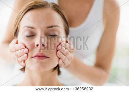 Midsection of masseur doing massage on woman at spa
