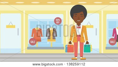 African-american woman holding shopping bags on the background of boutique window with dressed mannequins. Happy young woman carrying shopping bags. Vector flat design illustration. Horizontal layout.