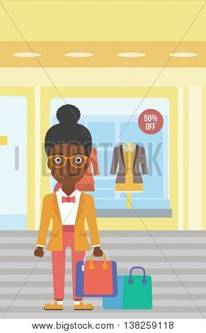 African-american woman holding shopping bags on the background of boutique window with dressed mannequins. Happy young woman carrying shopping bags. Vector flat design illustration. Vertical layout.