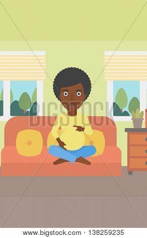 An african-american pregnant woman holding her hands on belly. Young pregnant woman sitting on a sofa at home. Vector flat design illustration. Vertical layout.
