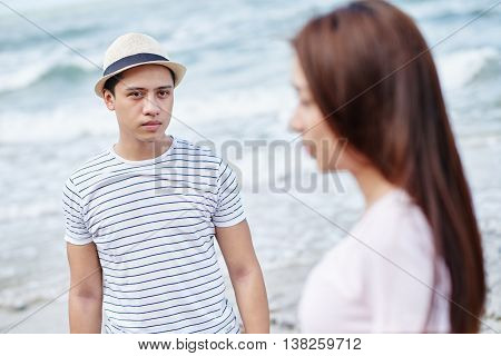 Unhappy handsome man looking at his girlfriend