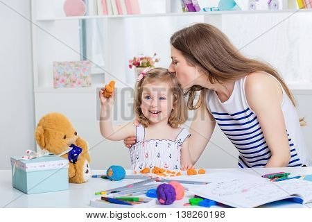 beautiful young mother and her little daughter playing with colored plasticine and drawing with crayons on the album. mother kissing baby