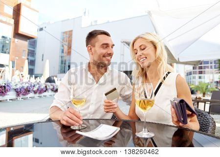date, people, relations and finances concept - happy couple with wallet, credit card and wine glasses paying bill at restaurant