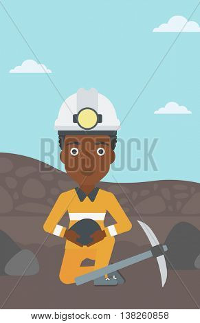 An african-american female miner in hard hat sitting with coal in hands and a pickaxe on the background of coal mine. Vector flat design illustration. Vertical layout.