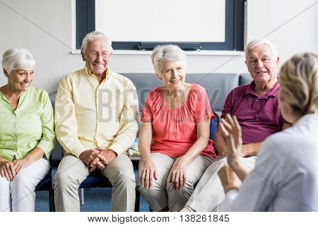 Seniors listening to nurse in a retirement home