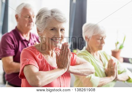 Seniors doing yoga with closed eyes in a retirement home