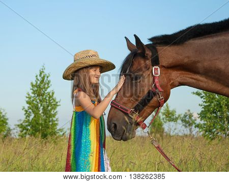 Little girl in a cowboy hat petting a horse