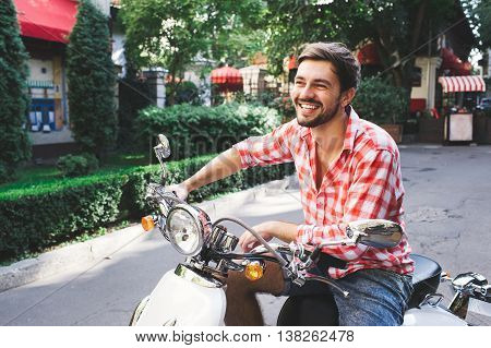 Handsome man riding a scooter on city roads. Summer potrait of male hipster with beard wearing a red shirt sitting on white retro motorbike