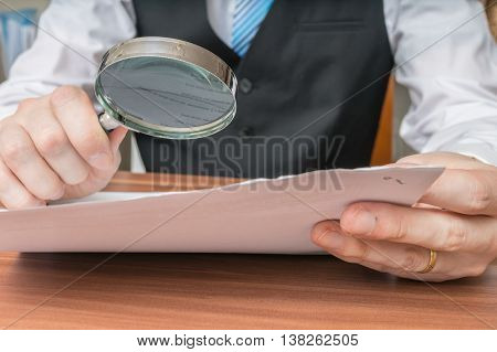 Businessman Is Inspecting Contract With Magnifying Glass.