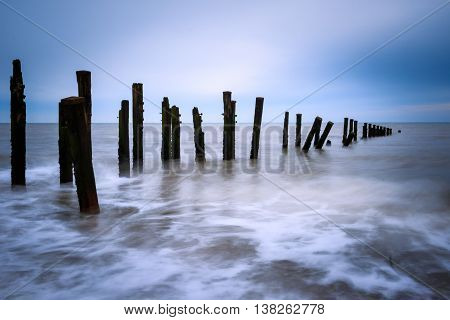 Wooden groynes on the beach with long exposure.