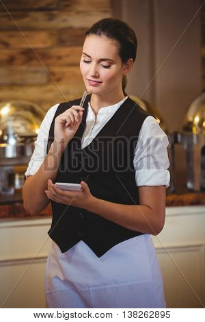 Waitress taking order on a notebook in a restaurant