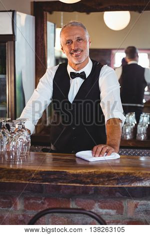 Portrait of smiling bartender cleaning bar counter