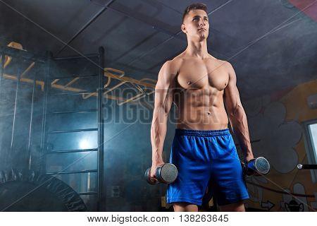 Muscular man posing, showing a beautiful body in modern gym
