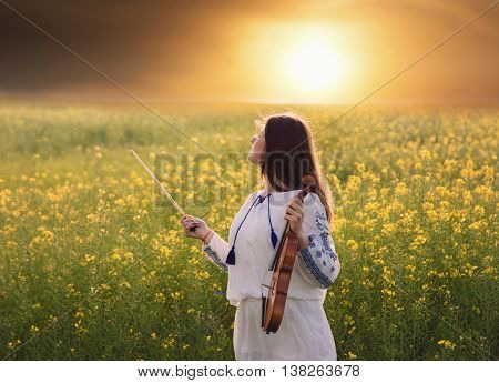 Young woman holding a violin in her hands, in a field, at sunset
