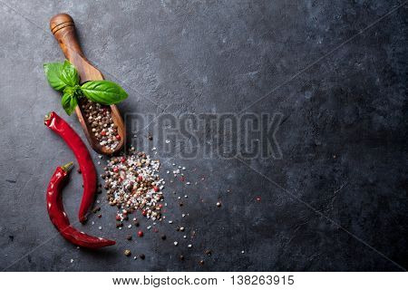 Pepper and salt spices, basil herb and chili pepper. Red, white and black peppercorn. On dark stone table. Top view with copy space