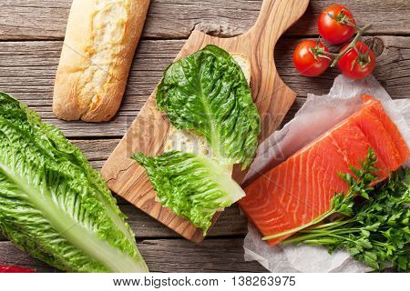 Sandwich cooking with ciabatta bread, salmon and romaine salad on wooden table. Top view