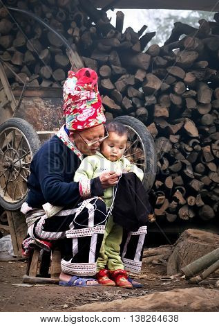 YEN BAI, Vietnam May 25, 2016 she and her grandson, the Dao, Mu Cang Chai high mountains, Yen Bai province, sitting embroidered brocade