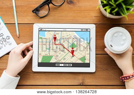 business, technology, people and navigation concept - close up of woman with gps navigator map on tablet pc computer screen and coffee on wooden table