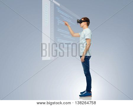 3d technology, virtual reality, entertainment, cyberspace and people concept - happy young man with virtual reality headset or 3d glasses playing game and touching screen with coding