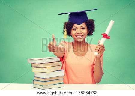 education, school, graduation, gesture and people concept - happy smiling african american student girl in bachelor cap with books and diploma showing thumbs up over green chalk board background