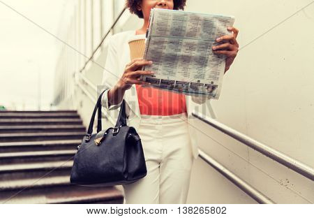 business, drinks, lifestyle and people concept - close up of young african american businesswoman with coffee cup and newspaper walking downstairs to city subway