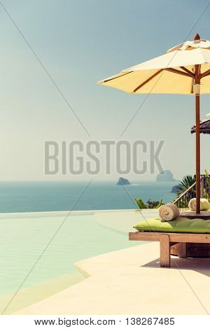 travel, vacation, tourism and luxury concept - beautiful view from infinity edge pool with parasol at seaside