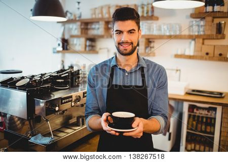 Portrait of smiling man standing with a cup of coffee in office cafeteria