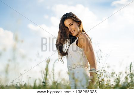 Beautiful woman without pollen allergy in chamomile field