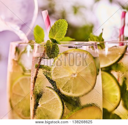 Alcohol drink. On wooden boards top of three glasses with alcohol drink and ice cubes. A drink number hundred thirty nine cocktail mohito with knife and mint leaf. Country life. Light background.