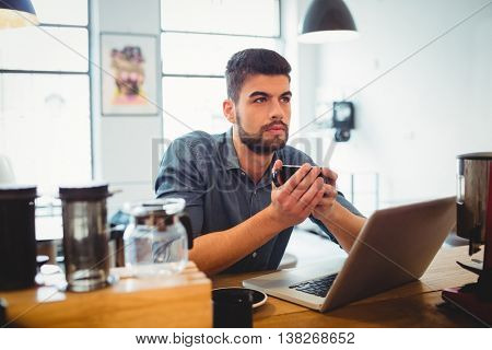 Thoughtful man having cup of coffee with laptop on table at cafeteria