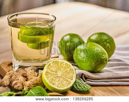 Healthy detox drink with ginger cocktail . On wooden boards glass with green tea and mint. A mint ginger drink number hundred thirty seven with half lime on napkin. Country life. Light background.