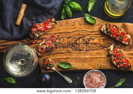 Tomato and basil bruschetta with glass of white wine served with olive oil, salt and fresh herbs on olive wooden board over black background, top view, copy space, horizontal composition