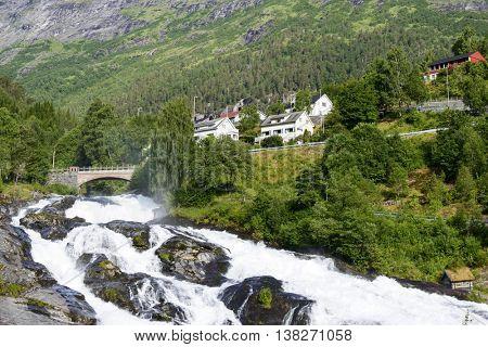 Bridge in Hellesylt on rushing mountain river.