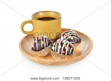 chocolate ball with a cup of coffee on wooden plate with white background