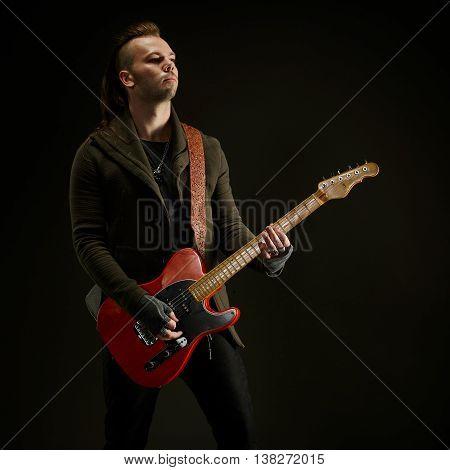 Guitarist playing rock music. On dark background. Beautiful guitar.