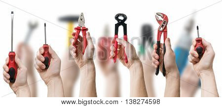 Many Hands Holds Up Instruments And Tools On Blurry Background.