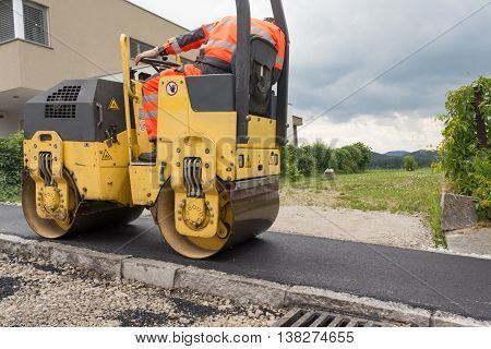 Worker at asphalting works with road roller