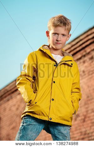 Cool modern eight-year boy posing over blue sky. Kid's fashion.