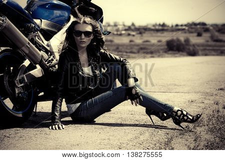Black-and-white portrait of a beautiful biker woman sitting by her motorcycle on a highway. The spirit of freedom and independence.